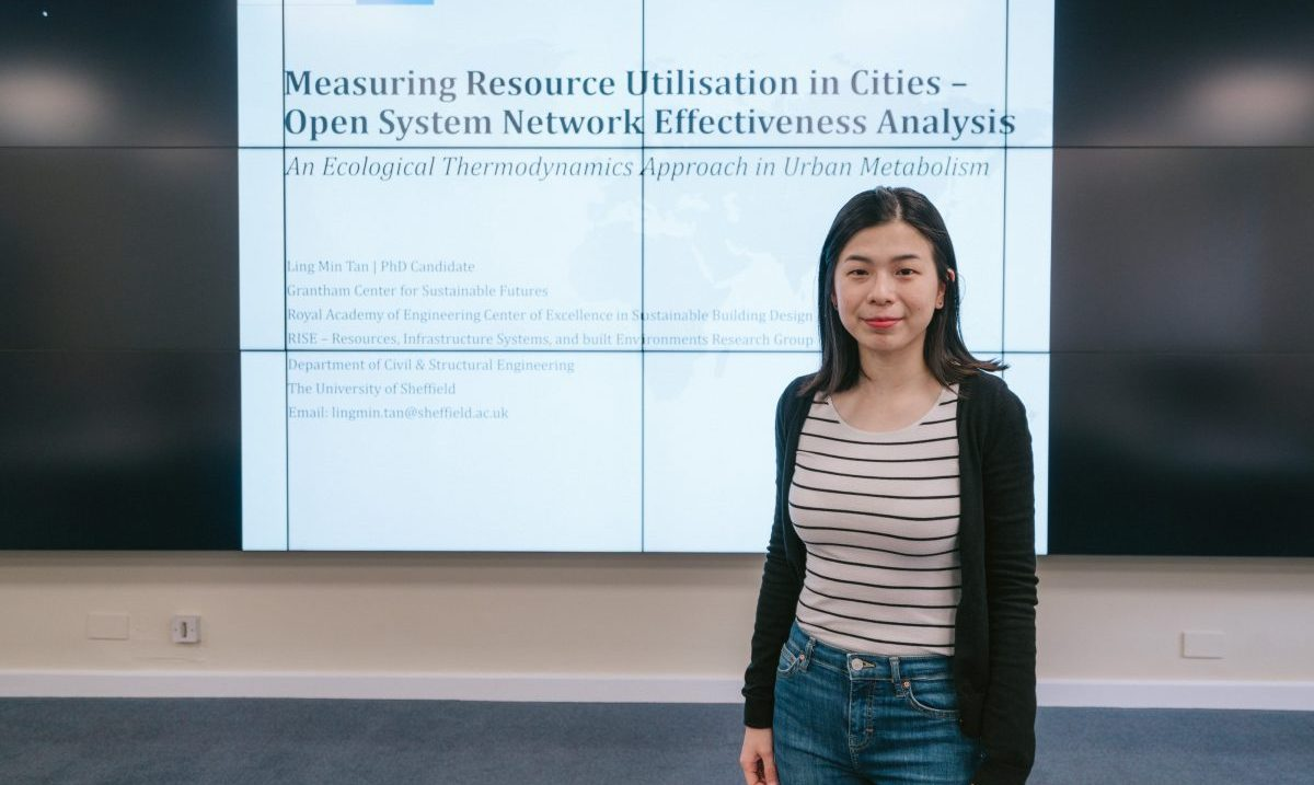 Ling Min in front of a power point presentation of her work