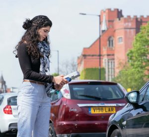 Maria standing near a busy road using her pollution measuring tool
