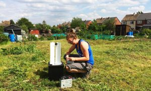 Emilie doing fieldwork with moths. We see Emilie in someone's back garden with a small moth trap.