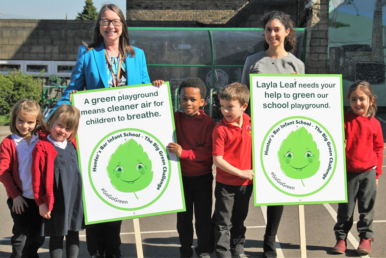 Children and team members pose with posters about the BREATHE green barrier project.