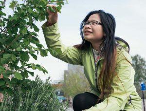 Maria Wang looks very happy as she examines plants
