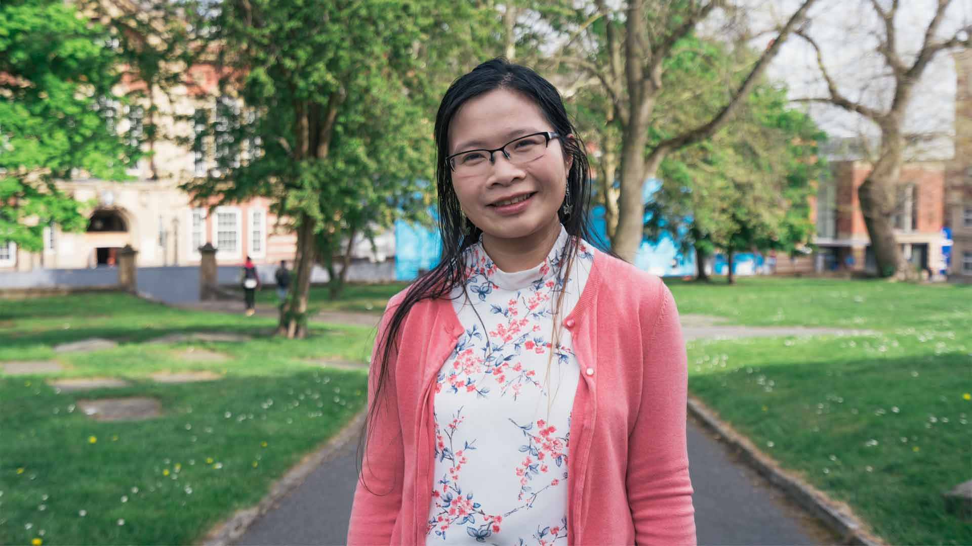 A photograph of Maria Wang Mei Hua who researches rubber, agroforestry and sustainability. She is pictured on TUoS campus and there are some nice trees behind her.